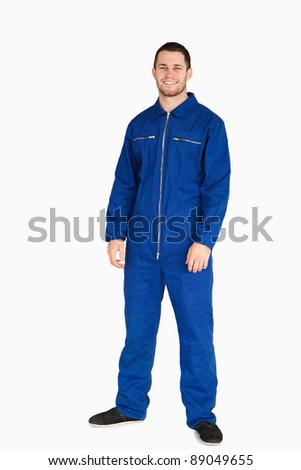 Smiling young mechanic in boiler suit against a white background