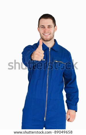 Smiling young mechanic in boiler suit giving thumb up against a white background