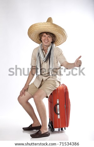 Smiling young mexican man with sombrero hitchhiking and sitting on his luggage