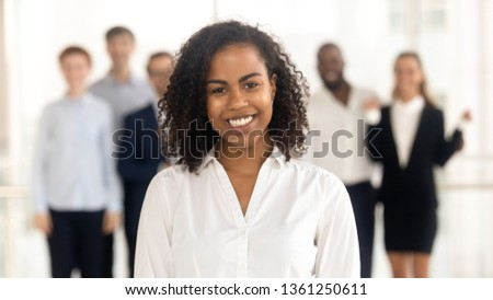 Smiling young mixed race female office worker student intern standing looking at camera with team people at background, happy african american employee business coach millennial professional portrait