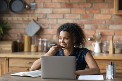 Smiling young mixed race woman dictating audio message in cellphone application, distracted from computer work at home. Happy multiracial lady holding loudspeaker conversation or sending voicemail.