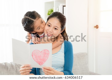 smiling young mom reading the mother's day gift card sitting on the living room sofa with little daughter kiss from behind at home. #634006517