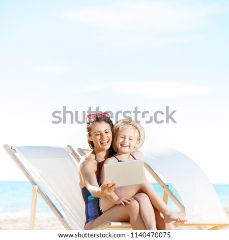 smiling young mother and child in swimsuit on the seacoast using tablet PC while sitting on beach chairs Foto stock ©