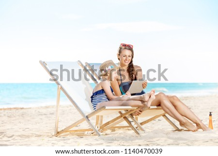 smiling young mother and child in swimwear on the seashore using tablet PC while sitting on beach chairs Foto stock ©