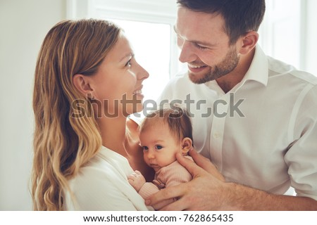 Smiling young mother and father standing in their living room at home affectionately cradling the cute baby girl in their arms