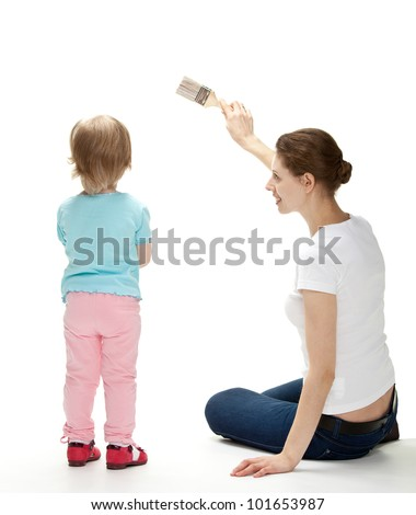 Smiling young mother and her little daughter painting the wall; white background