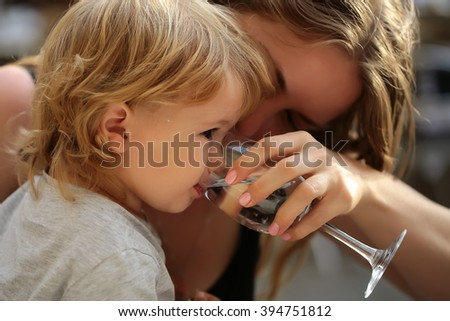 Smiling young mother holding glass and child boy with blonde hair drinking water from paret hands sunny day outdoor, horizontal picture