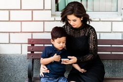 Smiling young mother holding her little son and using cell phone on bench.