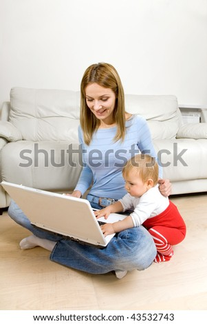 smiling young mother sitting with her daughter playing with laptop