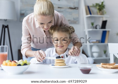 smiling young mother with cute little daughter eating pancakes for breakfast #697289029