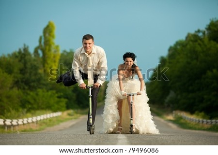 Smiling young newlywed couple with scooter on countryside road