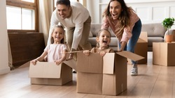 Smiling young parents ride happy little daughters in cardboard boxes play together on moving day, happy family with small girl kids have fun in living room relocating to new home, relocation concept
