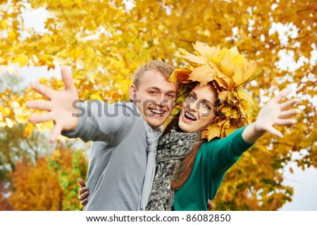 Smiling young people couple with open arms at fall outdoors. Woman wear autumn maple leaves wreath