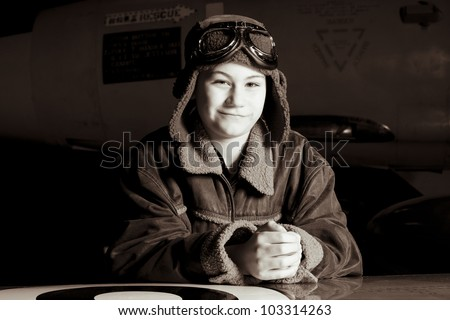Smiling young pilot with goggles resting on airplane wing, smiling at the camera