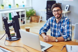 Smiling young programmer staring straight at camera while sitting at his desk
