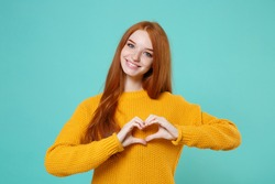 Smiling young redhead woman girl in yellow sweater posing isolated on blue turquoise wall background. People lifestyle concept. Mock up copy space. Showing shape heart with hands, heart-shape sign