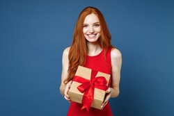 Smiling young redhead woman 20s in red elegant evening dress hold present box with gift ribbon bow isolated on blue background. St. Valentine's Day International Women's Day birthday, holiday concept