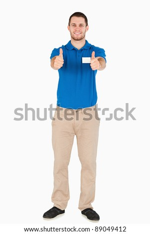 Smiling young sales assistant giving thumbs up against a white background