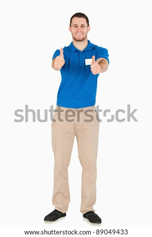 Smiling young salesman giving thumbs up against a white background