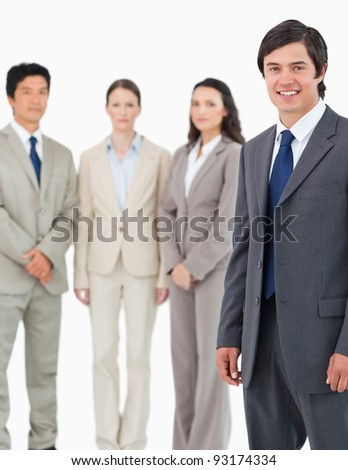 Smiling young salesman with his team behind him against a white background - stock photo