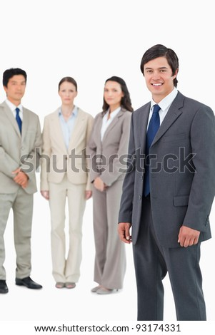 Smiling young salesman with team behind him against a white background
