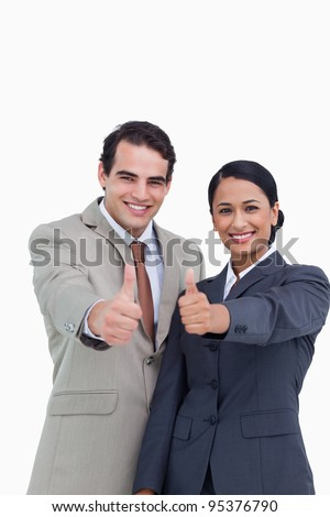 Smiling young salesteam giving thumbs up against a white background