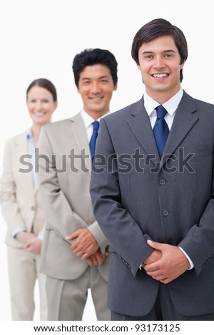 Smiling young salesteam standing in line against a white background