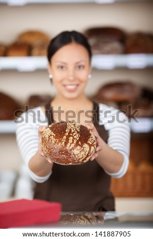 smiling young saleswoman showing bread in bakery