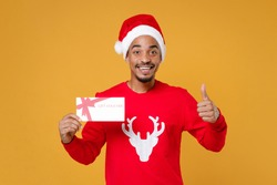 Smiling young Santa african american man in red sweater Christmas hat hold gift certificate showing thumb up isolated on yellow background studio. Happy New Year celebration merry holiday concept