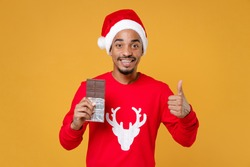 Smiling young Santa african american man in sweater Christmas hat hold chocolate bar showing thumb up isolated on yellow background studio portrait. Happy New Year celebration merry holiday concept