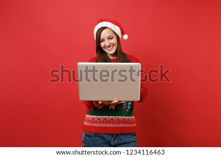Smiling young Santa girl in sweater Christmas hat using working on laptop pc computer isolated on bright red wall background. Happy New Year 2019 celebration holiday party concept. Mock up copy space