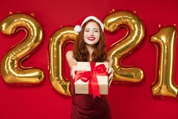 Smiling young Santa woman in elegant dress Christmas hat hold present box with gift ribbon bow isolated on red background golden numbers air balloons. New Year 2021 celebration holiday party concept