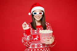 Smiling young Santa woman in sweater Christmas hat 3d glasses watching movie film hold bucket of popcorn isolated on red background studio portrait. Happy New Year celebration merry holiday concept