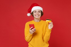 Smiling young Santa woman in yellow sweater Christmas hat using mobile cell phone hold credit bank card isolated on red background studio portrait. Happy New Year celebration merry holiday concept