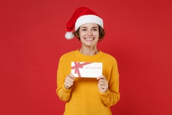 Smiling young Santa woman wearing casual yellow sweater Christmas hat hold gift certificate looking camera isolated on red background studio portrait. Happy New Year celebration merry holiday concept