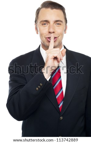 Smiling young smart business representative gesturing silence