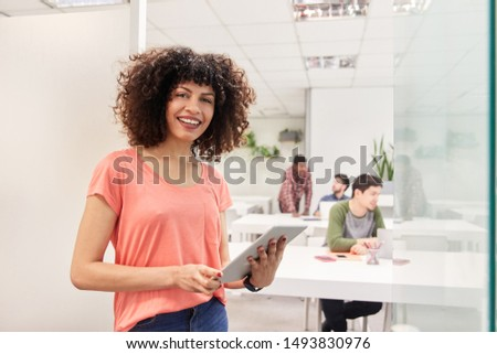 Smiling Young Start Up Business Woman Using Tablet Computer In Coworking Office