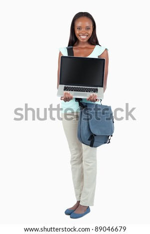 Smiling young student showing her laptop against a white background