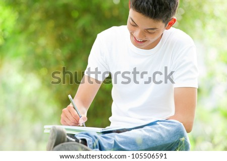 Smiling young student studying outside