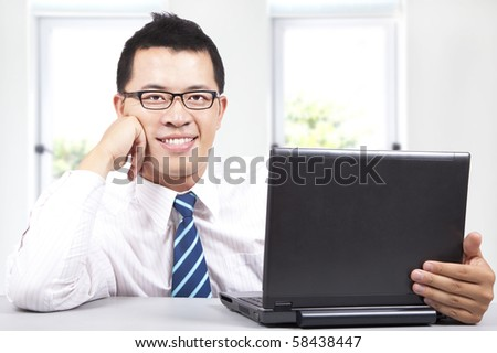 smiling young success businessman work with computer