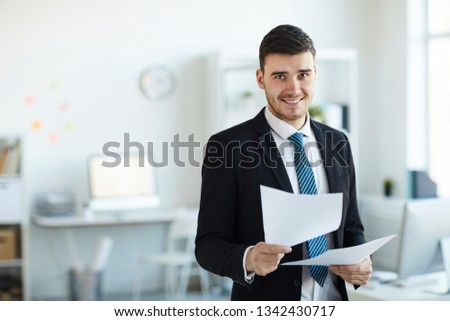 Smiling young successful banker in elegant suit looking through financial documents in office Stock photo ©