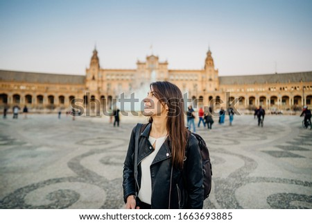 Smiling young tourist woman posing  at Plaza de Espana  in, Seville (Sevilla), Andalusia, Spain.Traveling to Spain.Sunset on Spain Square.Female  traveler visiting Spain,city break travel.