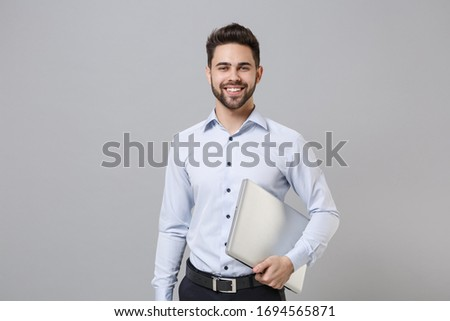 Smiling young unshaven business man in light shirt posing isolated on grey wall background studio portrait. Achievement career wealth business concept. Mock up copy space. Hold laptop pc computer
