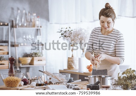 Smiling young woman adding noodles to pot while cooking in the kitchen #759539986