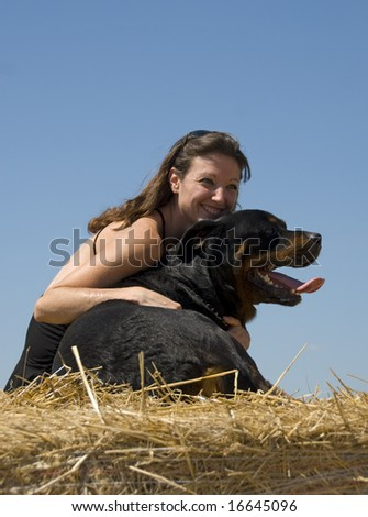 smiling young woman and her big black dog purebred rottweiler