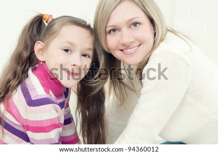 Smiling young woman and her daughter sitting in front of each other and looking at camera
