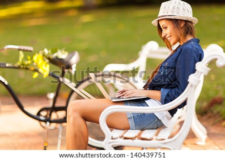 smiling young woman at the park using laptop