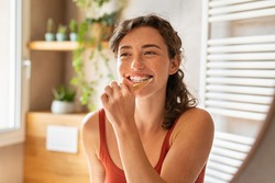 Smiling young woman brushing teeth in bathroom. Happy girl looking in mirror while using ecological toothbrush with whitening toothpaste. Beauty girl in bathroom cleaning teeth in the morning time.