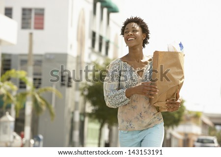 Smiling young woman carrying grocery bag while walking on street