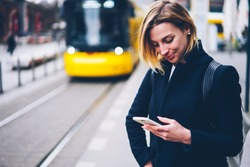 Smiling young woman checking table of city traffic online on web page using smartphone,positive hipster girl satisfied with app for paying for electric transport via cellphone waiting for tram